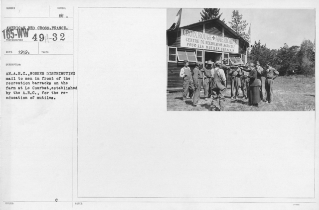 American Red Cross - Rehabilitation - An A.R.C. worker distributing mail to men in front of the recreation barracks on the farm at Le Courbat, established by the A.R.C. for the re-education of mutiles