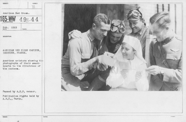 "American Red Cross - ""Second Aid"" - American Red Cross Canteen, Issoudun, France. American aviatiors showing the photographs of their sweethearts to the directress of the canteen"