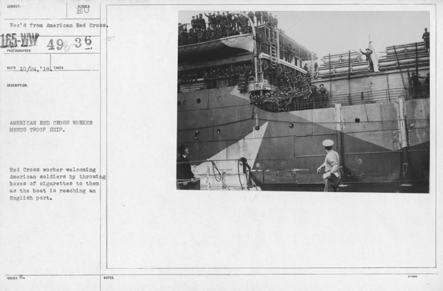 """American Red Cross - """"Second Aid"""" - American Red Cross worker meets troop ship. Red Cross worker welcoming American soldiers by throwing boxes of cigaretes to them as the boat is reaching an English port"""