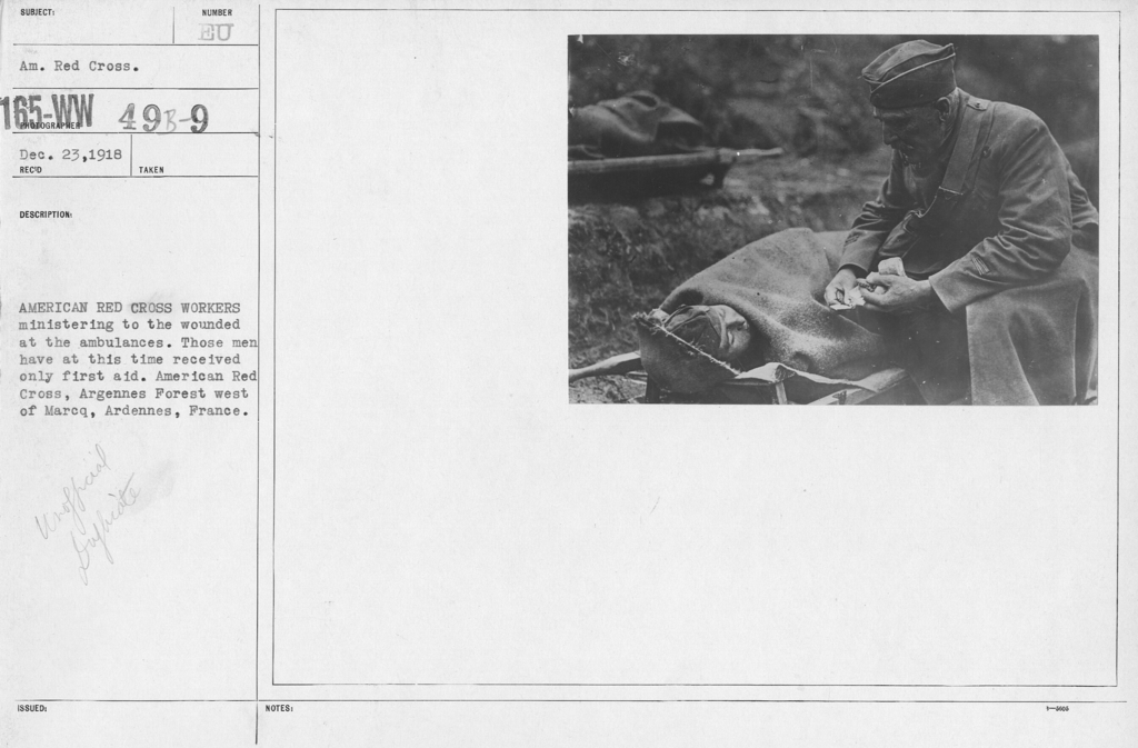 """American Red Cross - """"Second Aid"""" - American Red Cross workers ministering to the wounded at the ambulances. Those men have at this time received only first aid. American Red Cross, Argennes Forest west of Marcq, Ardennes, France"""