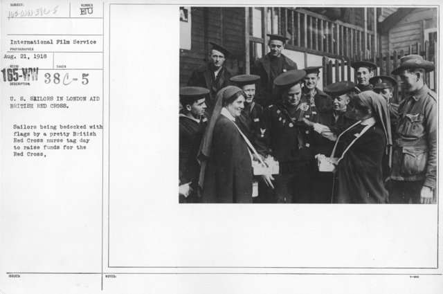 American Red Cross - Soliciting Funds - Personal Appeal - U.S. Sailors in London and British Red Cross. Sailors being bedecked with flags by a pretty British Red Cross nurse tag day to raise funds for the Red Cross