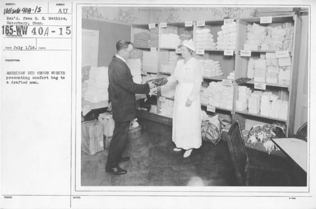American Red Cross - Supplies - American Red Cross worker presenting comfort bag to a drafted man