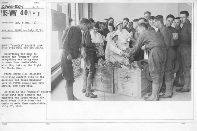 """American Red Cross - Supplies - Happy """"Sammies"""" receive comfort kits from the Red Cross. Everything was done to assure the """"Sammies"""" that everything was being done to make them comfortable when they take up the fight for Uncle Same. Photo shows U.S. soldiers receiving comfort kits in the American Red Cross Headquarters at Fifth avenue and 37th street, New York City. As soon as the """"Sammies"""" received their kits they scanned the contents and found within almost every little item that tends to make them cofortable. July 27, 1917"""