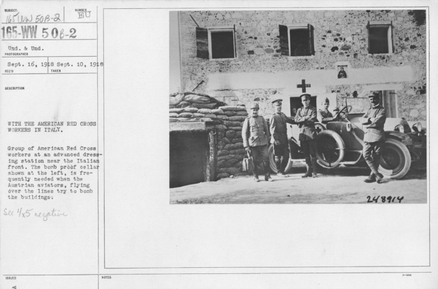 American Red Cross - Vehicles - With the American Red Cross workers in Italy. Group of American Red Cross workers at an advanced dressing station near the Italian front. The bomb proof cellar shown at the left, is frequently needed when the Austrian aviators, flying over the lines try to bomb the buildings