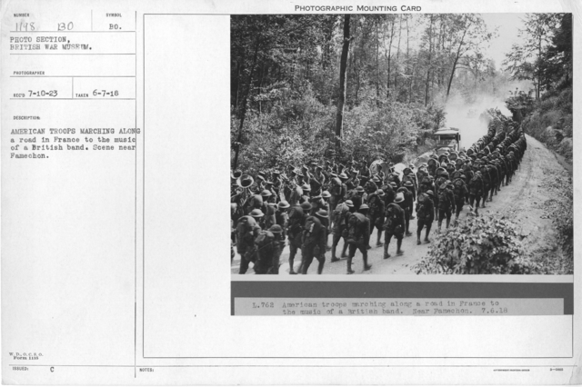American troops marching along a road in France to the music of a British band. Scene near Famechon