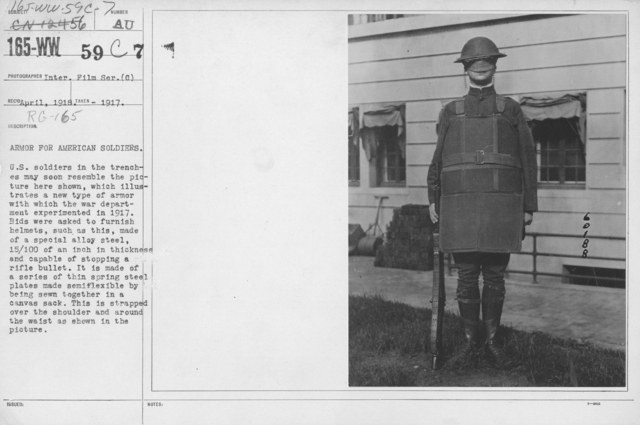 Armor - Body and Helmets - Armor for American soldiers. U.S. soldiers in the trenches may soon resember the picture here shown, which illustrates a new type of armor with which the war department experimented in 1917. Bids were asked to furnish helmets, such as this, made of a special alloy steel, 15/100 of an inch in thickness and capable of stopping a rifle bullet. It is made of a series of thin spring steel plates made semiflexible by being sewn together in a canvas sack. This is strapped over the shoulder and around the waist as shown in the picture