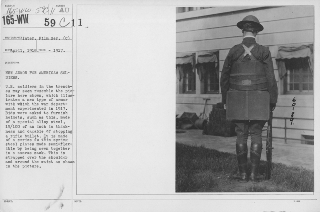 Armor - Body and Helmets - New armor for American soldiers. U.S. soldiers in the trenches may soon resember the picture here shown, which illustrates a new type of armor with which the war department experimented in 1917. Bids were asked to furnish helmets, such as this, made of a special alloy steel, 15/100 of an inch in thickness and capable of stopping a rifle bullet. It is made of a series for thin spring steel plates made smi-flexible by being sewn together in a canvas sack. This is strapped over the shoulder and around the waist as shown in the picture