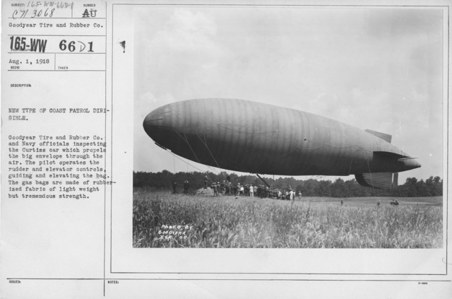 Balloons - Miscellaneous - New type of Coast Patrol Dirigbile. Goodyear Tire and Rubber Co. and Navy officials inspecting the Curtiss car which propels the big envelope through the air. The pilot operates the rudder and elevator controls, guiding and elevating the bag. The gas bags are made of rubberized fabric of light weight but tremendous strength