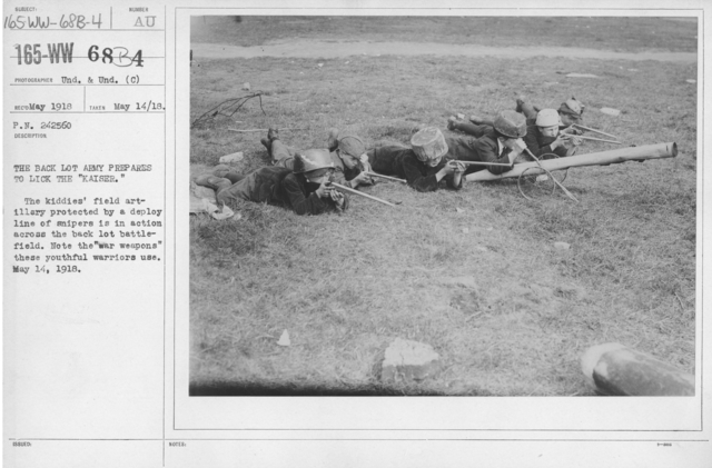 """Boy's Activities - Drills - The back lot Army prepares to lick the """"Kaiser."""" The kiddies' field artillery protected by a deploy line of snipers is in action across the back lot battlefield. Note the """"war weapons"""" these youthful warriors use. May 14, 1918"""