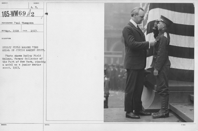 Boy's Activities - Junior Camp Association - Dudley Field fmalone pins medal on Junior Marine Scout. Photo shows Dudley Field Malone, former Collector of the Port of New York, pinning a medal on a junior Marine scout. 1917