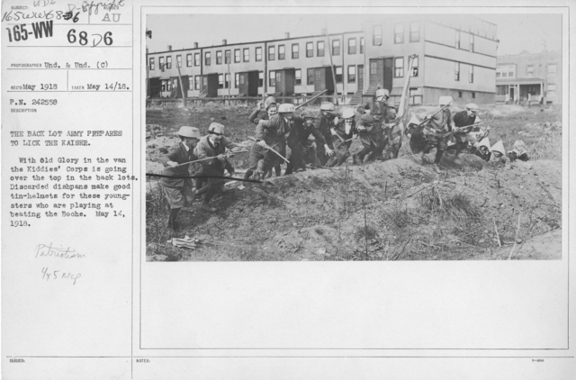 Boy's Activities - Patriotism - The back lot Army prepares to lick the Kaiser. With Old Glory in the van the Kiddies' Corps is going over the top in the back lots. Discarded dishpans make good tin-helmets for these youngsters who are playing at beating the Boche. May 14, 1918