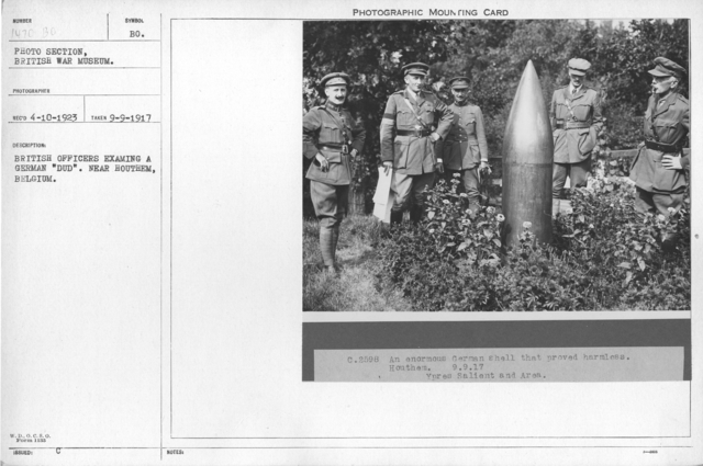 "British officers examining a German ""Dud"". Near Houthem, Belgium"