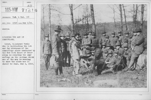 Camouflage - Soldiers Training - Learning the art of camouflage. Lieut. H. Ledyard Towle who is instructing the 1st and 2nd platoons of the camouflage class conducted by the New York Board of Education is painting the camouflage on the costume which one of the men is wearing to show the class how it should be done. May 1, 1918