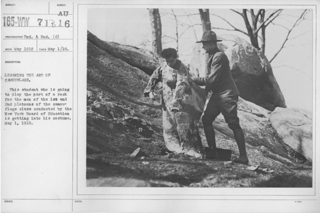 Camouflage - Soldiers Training - Learning the art of camouflage. This student who is going to play the part of a rock for the men for the 1st and 2nd platoons of the camouflage class conducted by the New York Board of Education is getting into his costume. May 1, 1918