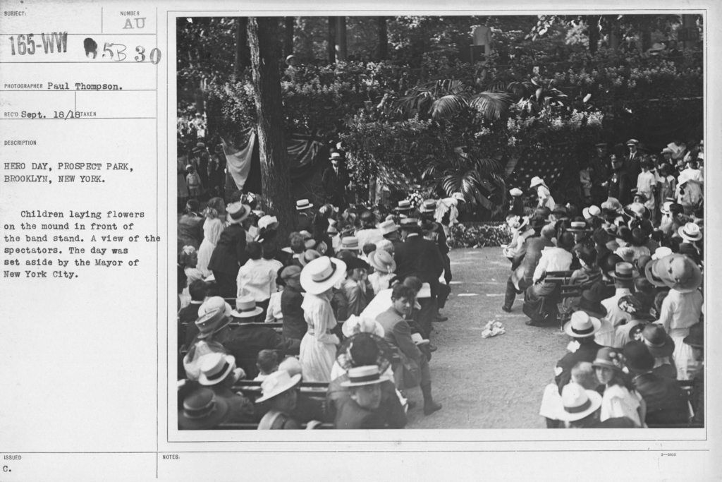 Ceremonies and Parades - Hero Day , Prospect Park, Brooklyn, New York.  Children laying flowers on the mound in front of the band stand.  A view of the spectators.  The day was set aside by the Mayor of New York City