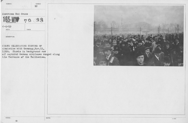 Ceremonies - France - Crowd celebrating signing of armistice with Germany, Nov. 11, 1918. Show's in background row of captured German airplanes ranged along the Terrace of the Tuilleries