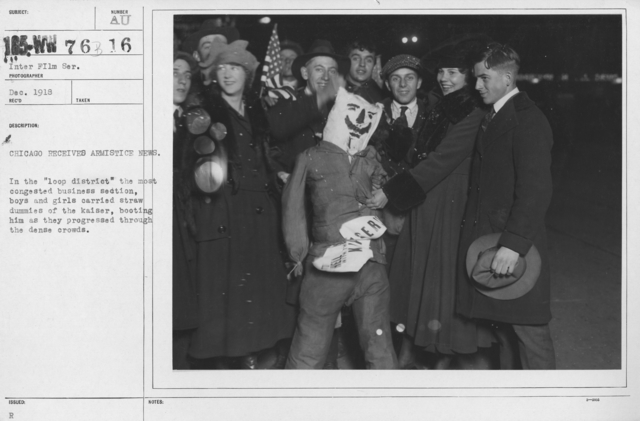 """Ceremonies - Illinois - Chicago Peace Demonstrations - Chicago receives Armistice News. In the """"loop district"""" the most congested business section, boys and girls carried straw dummies of the kaiser, booting him as they progressed through the dense crowds"""