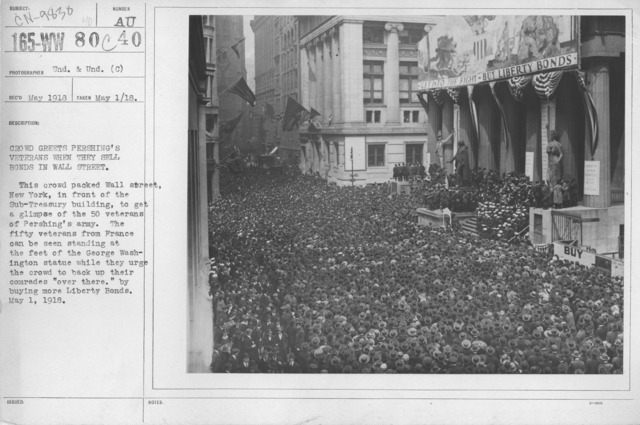"""Ceremonies - Liberty Loans (War Finance Parade) - Crowd greets Pershing's veterans when they sell bonds in Wall Street. This crowd packed Wall Street, New York, in front of of the Sub-Treasury building to get a glimpse of the 50 veterans of Pershing's army. The fifty veterans form France can be seen standing at the feet of the George Washington statue while they urge the crowd to back up their comrades """"over there"""" by buying more Liberty Bonds. May 1, 1918"""
