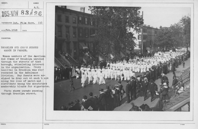 Ceremonies - New York - Brooklyn Red Cross nurses march in parade. Women members of the American Red Cross of Brooklyn marched through the streets of the borough, stimulating interest in the organization. Every hospital in Brooklyn was preresented in the Ambulance Division. Boy Scouts were assigned to drop out at each block along the line of march and distribute among the spectators membership blanks for signatures. Photo shows parade passing through Brooklyn Street