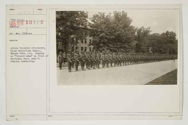 "Colleges and Universities - Bliss Electrical School, Takoma Park, Washington D.C. - Second Training Detachment, Bliss Electrical School, Takoma Park, D.C.  Company at ""Present Arms"" in front of barracks, Captain Chas. F. Johnson Commanding"