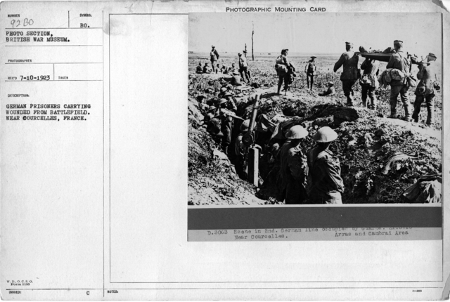 German prisoners carrying wounded from battlefield. Near Courcelles, France