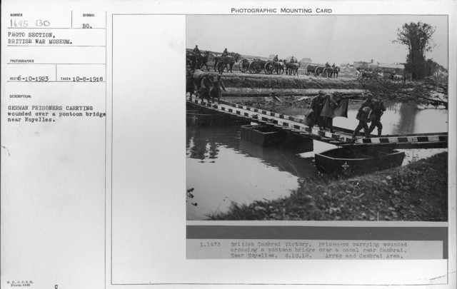 German prisoners carrying wounded over a pontoon bridge near Noyelles. 10-8-1918
