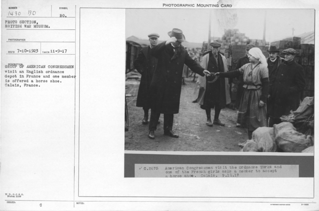 Group of American congressmen visit an English ordinance depot in France and one member is offered a horse shoe, Calais, France