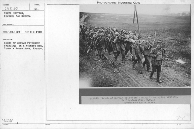 Group of German prisoners bringing in a wounded man. Somme - Ancre Area, France. 8-8-1918