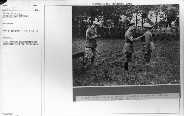 King George decorating an American soldier in France. 8-12-1918