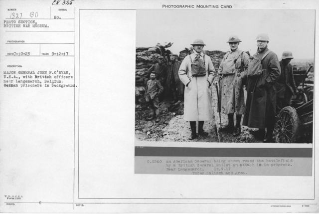 Major General John F. O'Ryan, U.S.A. with British officers near Langemarch, Belgium. German prisoners in background. 9-12-1917