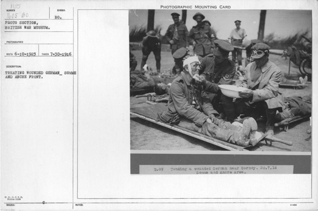Treating wounded German, Somme and Ancre front. 7-30-1916
