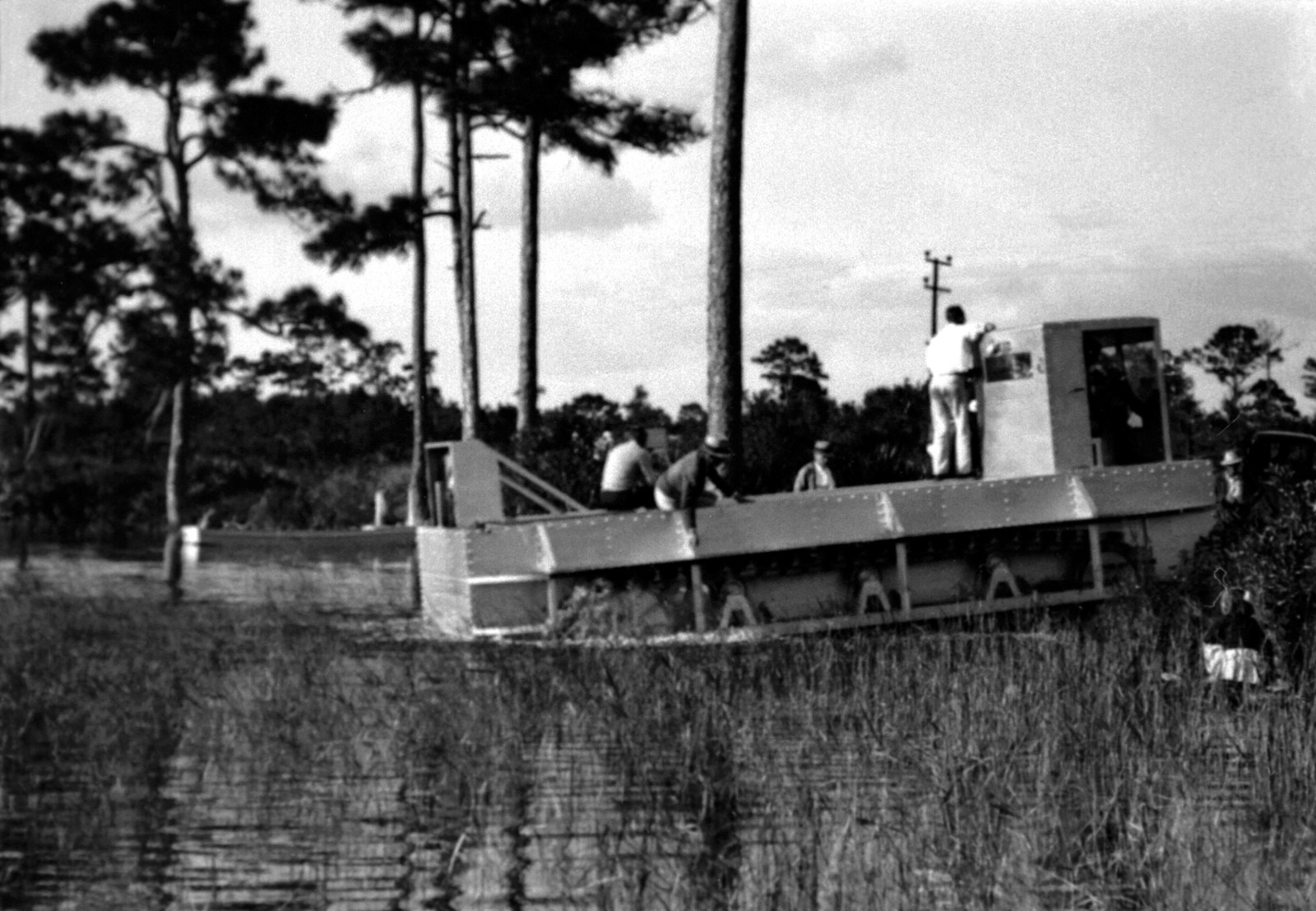A side view of the Roebling Alligator tractor as it moves through a swampy area. The tractor is a Donald Roebling creation and is the vanguard for the present Marine LVTP-7 tracked landing vehicle