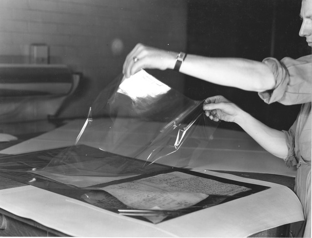 Photograph of Staff Preparing Damaged Documents for Lamination, Division of Repair and Preservation at the National Archives