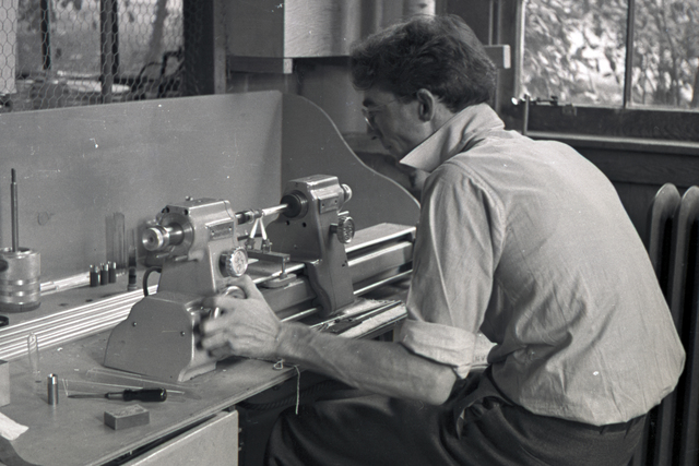 Charles Litton working on a glass blowing lathe of his design which revolutioized the vacuum tube industry. Founder of Litton Industries. Cooksey  21-1, November 16, 1937. [Photographer: Donald Cooksey]
