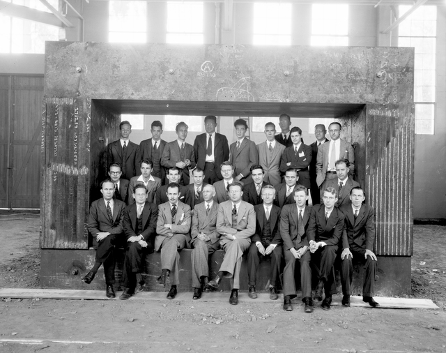 Early Radiation Laboratory staff framed by the magnet for the 60-inch cyclotron in 1938. Front row, left to right: John H. Lawrence, Robert Serber, Franz N.D. Kurie, Raymond T. Birge, Ernest O. Lawrence, Donald Cooksey, Arthur H. Snell, Luis W. Alvarezz, Philip H. Abelson. Second row: John Backus, Wilfred B. Mann, Paul C. Aebersold, Edwin M. McMillan, Ernest Lyman, Martin D. Kamen, D.C. Kalbfell, W.W. Salisbury. Back row: Alex S. Langsdorf, Jr., Sam Simmons, Joseph G. Hamilton, David H. Sloan, J. Robert Oppenheimer, William Brobeck, Robert Cornog, Robert R. Wilson, Eugene Viez, J.J. Livingood. [Photographer: Donald Cooksey]