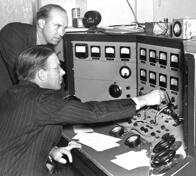 Ernest Orlando Lawrence and his brother John Lawrence (rear) at control panel of 60-inch cyclotron shortly after it began operation in 1938. Morgue 1958-8 (P-17). [Photographer: Donald Cooksey]