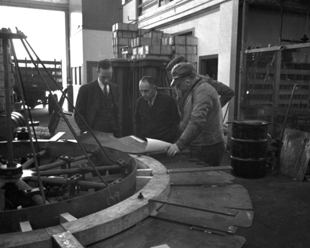 Bill Brobeck (left) l ooking at plans. Cooksey caption: First coil wound Jan 31st for Japan, Feb 2nd shorts found, Feb second completed rewinding Ist coil. Our Ist coil started April 13th - finished- delivered may 19th. Cooksey  22 - 26,  April 13, 1938. [Photographer: Donald Cooksey]