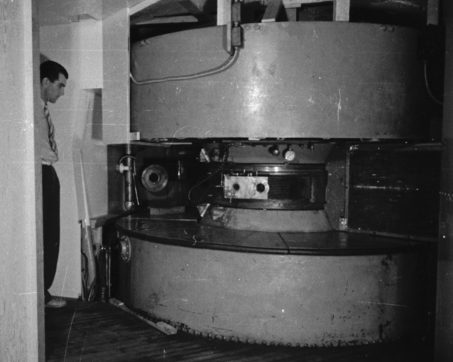 The 37-inch cyclotron accelerated deuterons to 8 MeV and alpha particles to 16 MeV. It was also used to create radio isotopes and the first artificial element, technetium. This cyclotron was  used in one of the first attempts to treat cancer. Shown with Paul Aebersold  looking on. Cooksey  label: Cancer Room, note proton snout. Cooksey 1-12, September 20, 1938. [Photographer: Donald Cooksey]