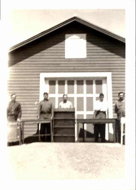 Men Standing behind Desks and a Bookshelf in front of a Garage
