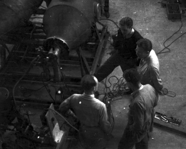 Thornton (back to camera), Ernest Orlando Lawrence, and  D.C. Kalbfell at 60-inch cyclotron tank. Cooksey  13-30,  Feburary 6, 1939. [Photographer: Donald Cooksey]