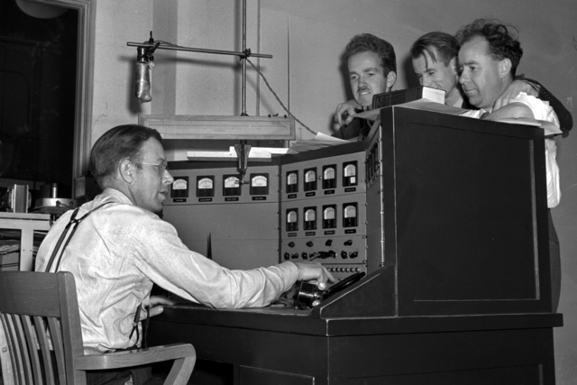 Ernest Orlando Lawrence at the controls of the 60-inch. cyclotron with Dr. Raymond, Edwin McMillan, and Winfield W. Salisbury standing behind control panel. Negative envelope dated June 12, 1939. Cooksey 17 [Photographer: Donald Cooksey]