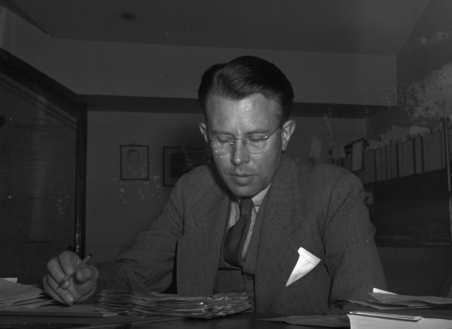 Ernest Orlando Lawrence writing at desk, taken November 15, 1939.  Damaged negative. Principal Investigator/Project: Analog Conversion Project [Photographer: Donald Cooksey]