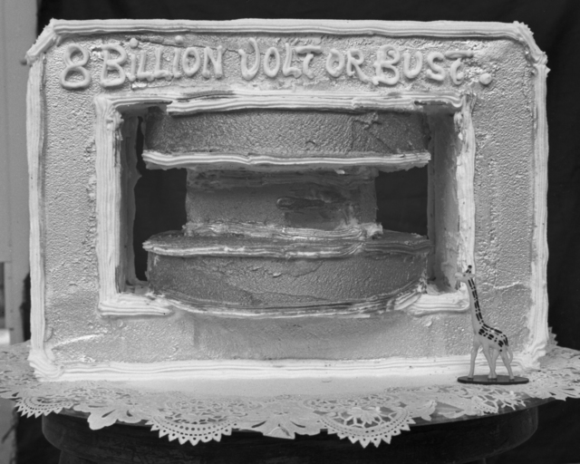 "DiBiasi Restaurant dinner cake. ""8 Billion Volt (cyclotron) or Bust,"" taken November 18, 1939. Radiation Lab dinner in honor of Ernest Orlando Lawrence for winning the Nobel Prize. Principal Investigator/Project: Analog Conversion Project [Photographer: Donald Cooksey]"