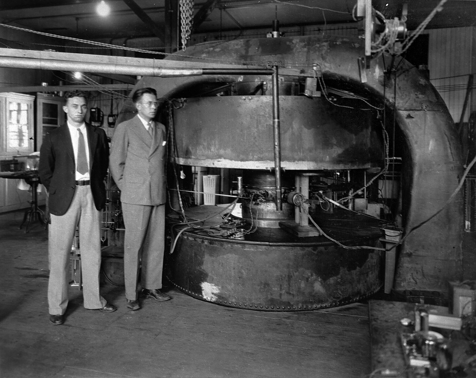 1933 - Standing before 74 tons of iron and copper are Professor M. Stanley Livingston (left) now of the Massachusetts Institute of Technology and Professor Ernest Orlando Lawrence.  Magnet development has continued to expanded more nearly to its capacity, producing the new nuclear particles known as neutrons in quantities sufficient for actual human therapy.  Negative envelope dated February 1, 1940. Principal Investigator/Project: Analog Conversion Project [Photographer: Donald Cooksey]