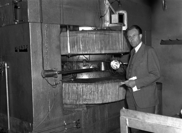 Ernest Orlando Lawrence standing next to cyclotron at Purdue. Negative envelope dated April 20, 1940. Principal Investigator/Project: Analog Conversion Project [Photographer: Donald Cooksey]