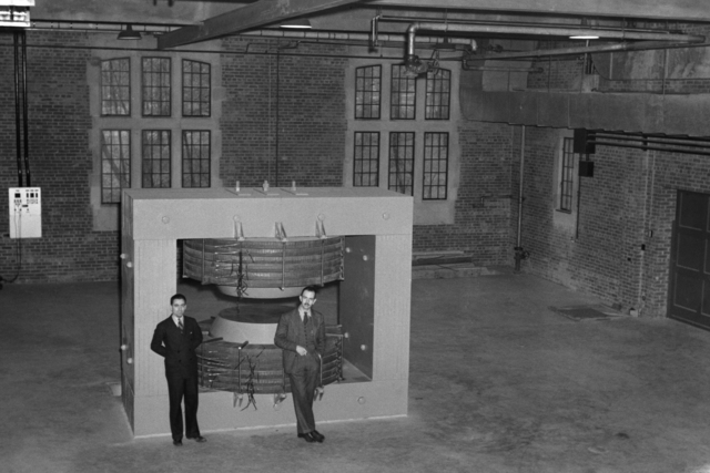 Indiana cyclotron with Larry Langer and Franz N.D. Kurie. Indiana University, involved in the construction of their first cyclotron, joined the Manhattan Project. Photo taken April 20, 1940. Principal Investigator/Project: Analog Conversion Project [Photographer: Donald Cooksey]