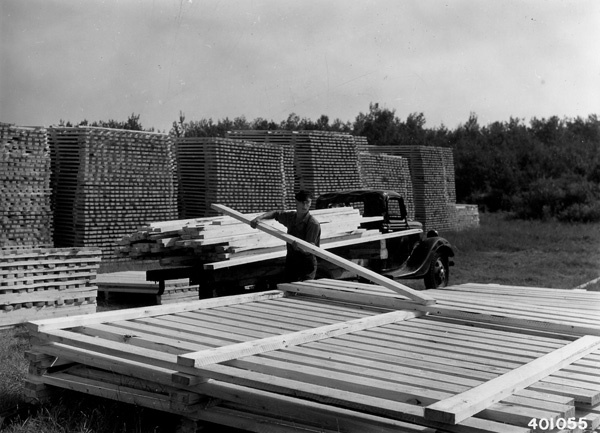 Photograph of Worker Piling Two-by-Six Red Pine Lumber