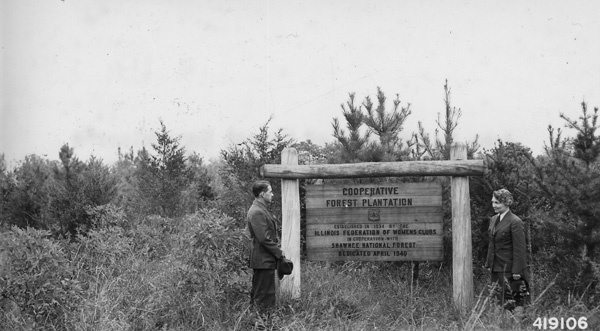 Photograph of John E. McQueen of Forest Supervisor's Staff and Miss March-Mount at a Sign for the Illinois Federation of Women's Clubs Cooperative Forest Plantation