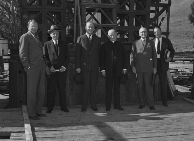Grounds and Buildings Committee of the Regents of the University of California in front of the184-inch cyclotron magnet pole inspecting progress after having accepted the Medical Physics (Donner Lab) site. Left to right: Ernest Orlando Lawrence, Mortimer Fleishhacker, Robert G. Sproul, (Reverend Monsiginor ) Charles Adolph Ramm, Sidney M. Ehrman, and Edward Augustus Dickson, taken May 21, 1941. Principal Investigator/Project: Analog Conversion Project [Photographer: Donald Cooksey]