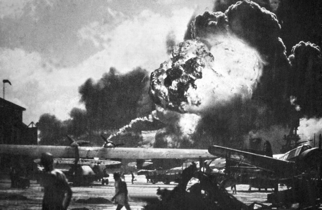 Aircraft at Hickam Field, Hawaii (HI) continue to burn and explode, in the immediate aftermath of the bombing of Pearl Harbor and other military installations